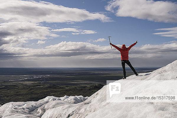 Erwachsener Mann steht im Skaftafell-Nationalpark auf dem Vatnajokull-Gletscher  Island  und hält einen Eispickel