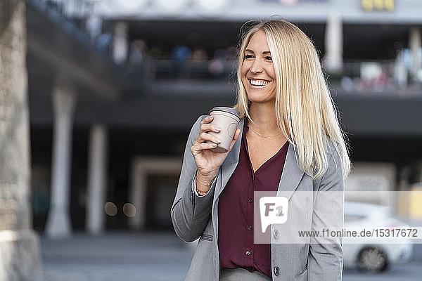 Porträt einer glücklichen blonden Geschäftsfrau mit Kaffee zum Mitnehmen