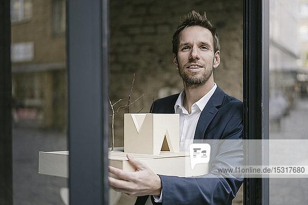 Portrait of businessman holding architectural model