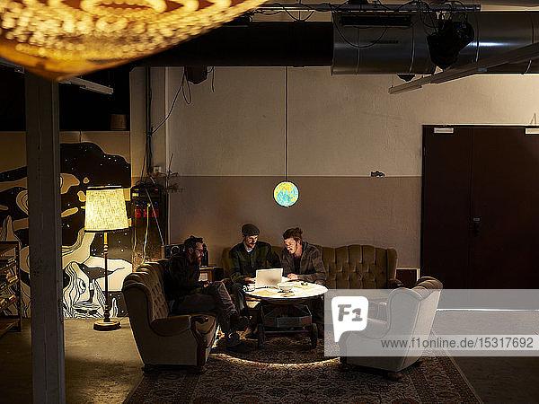 Drei Männer benutzen Laptop in einem Loft