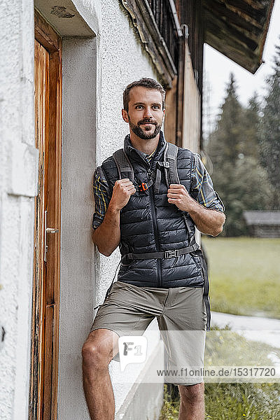 Young man at a farmhouse during a hiking trip  Vorderriss  Bavaria  Germany