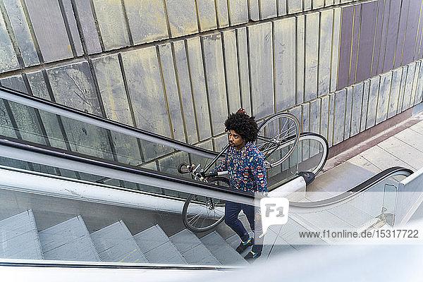 Eleganter Mann trägt Fahrrad auf Rolltreppe