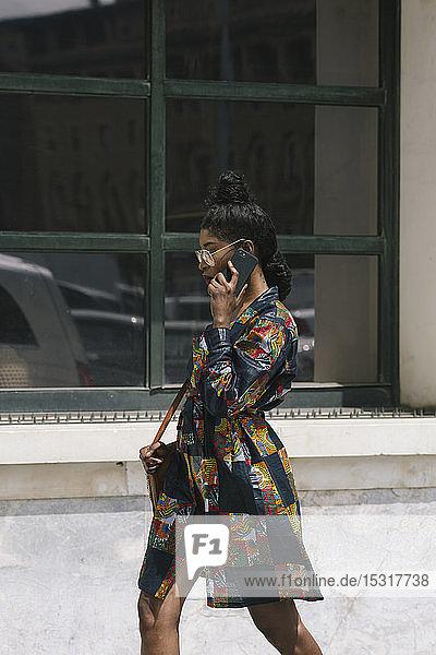 Porträt einer eleganten Frau in gemustertem Kleid  die mit dem Handy telefoniert