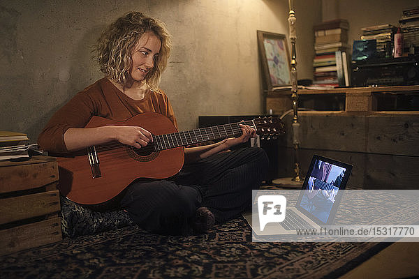 Lächelnde junge Frau sitzt mit Gitarre auf dem Boden und schaut auf den Laptop