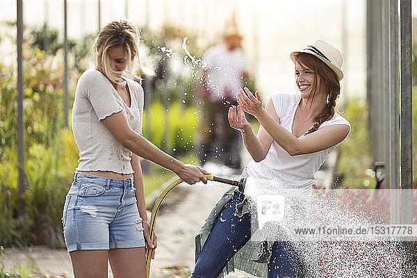 Zwei glückliche junge Frauen amüsieren sich im Gewächshaus beim Gießen der Blumen mit dem Schlauch