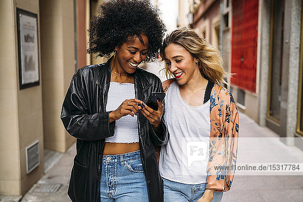 Multicultural happy women walking in the city  looking on smartphone