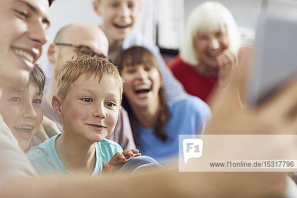 Kleiner Junge sieht sich mit seiner Familie ein digitales Tablet an