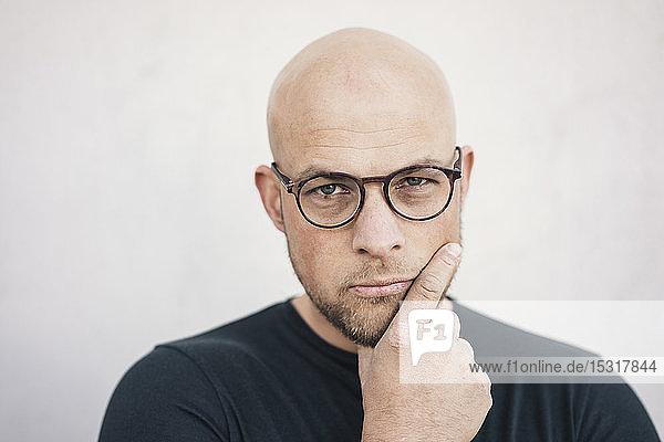 Portrait of starring bald man wearing glasses