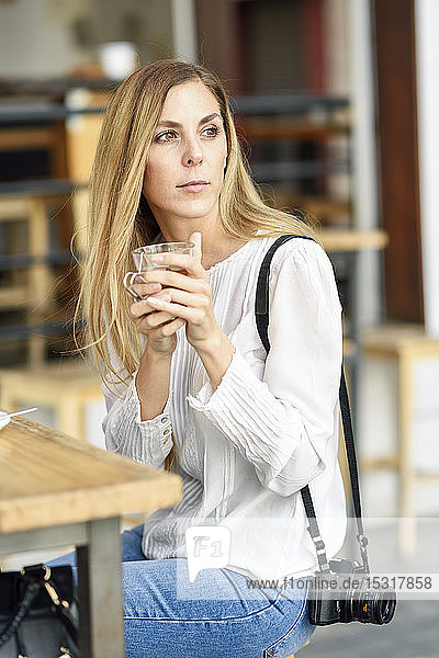 Woman drinking tea sitting at an outdoor table in a cafe