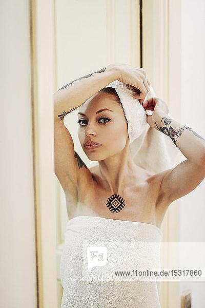 Porträt einer tätowierten Frau zu Hause mit in ein Handtuch gewickeltem Haar
