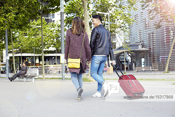 Tourists Couple holding hands and walking down the street with a wheel suitcase  Barcelona  Spain