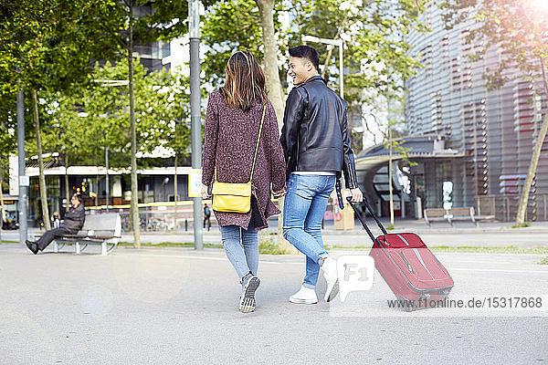 Touristenpaar  das sich an den Händen hält und mit einem Radkoffer die Straße entlang läuft  Barcelona  Spanien