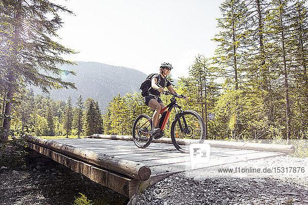 Frau fährt E-Mountainbike in den Bergen