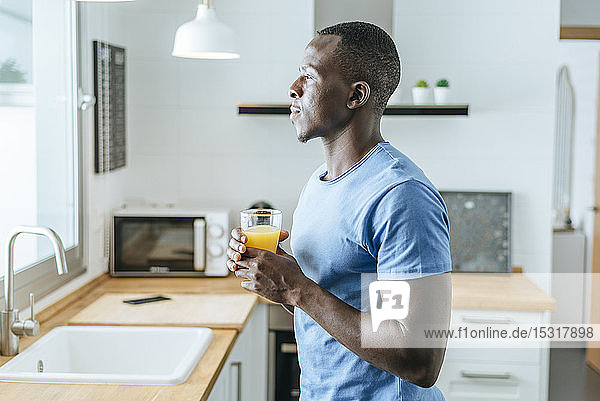 Young man with orange juice in kitchen at home
