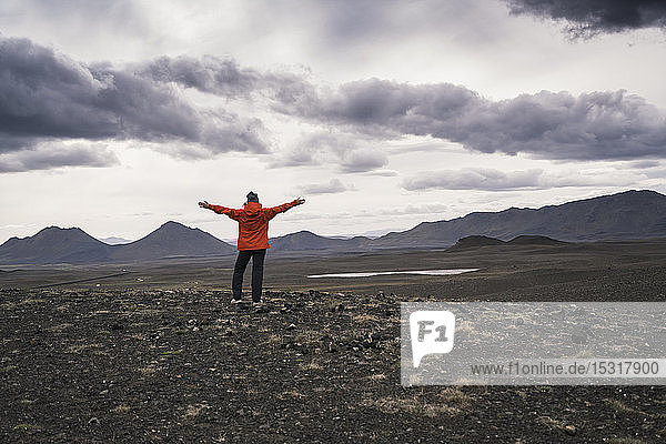 Young woman looking at view  with arms outstretched  Highland region  Iceland