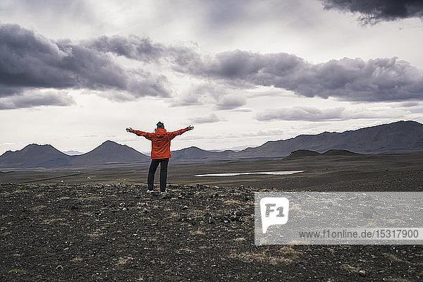 Junge Frau schaut mit ausgestreckten Armen auf die Aussicht  Hochlandregion  Island