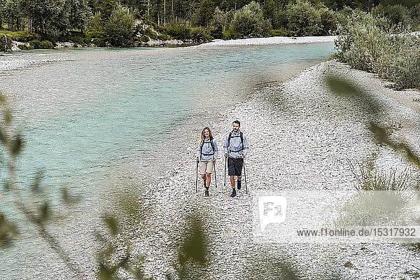 Young couple on a hiking trip walking at the riverside  Vorderriss  Bavaria  Germany