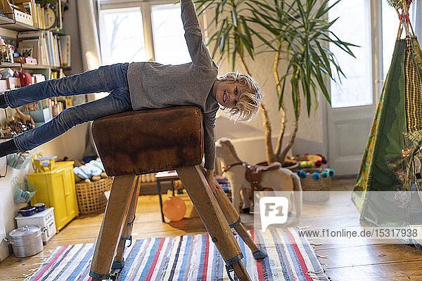 Porträt eines lächelnden Jungen  der auf einem Bock in seinem Zimmer zu Hause liegt