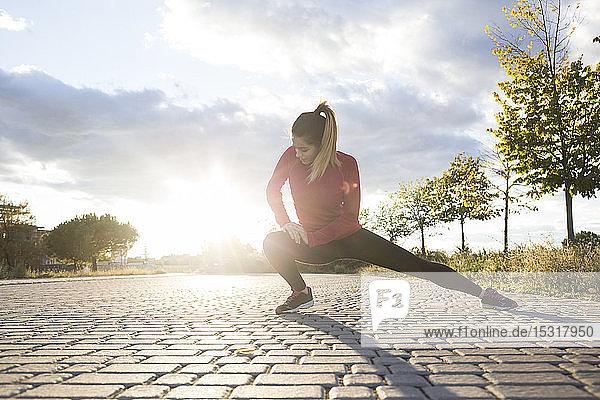 Junge Frau streckt ihr Bein in einem Park