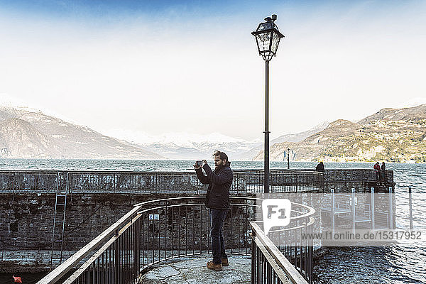 Man using mobile phone taking photos at Lake Como in winter  Italy
