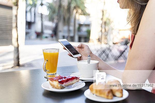 Junge Frau sitzt im Straßencafé und telefoniert