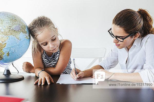 Lehrer hilft Schülerin am Schreibtisch beim Schreiben auf Papier