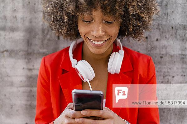 Porträt einer lächelnden jungen Frau mit Kopfhörer und Smartphone