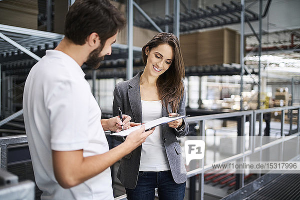 Man signing document in factory held by businesswoman