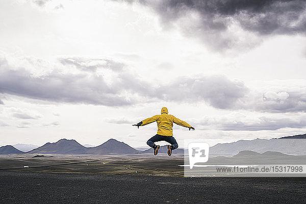 Reifer Mann springt vor Freude in der Hochlandregion  Island
