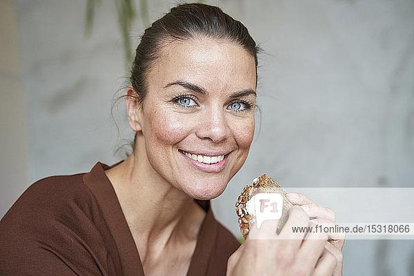 Porträt einer lächelnden Frau  die ein Sandwich isst