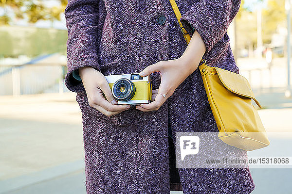 Close-up of woman holding a vintage analog camera