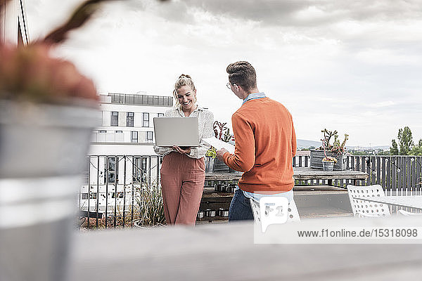 Casual businessman and woman with laptop meeting on roof terrace
