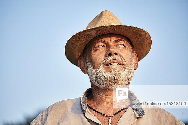Porträt eines nachdenklichen älteren Mannes mit Sommerhut im Freien