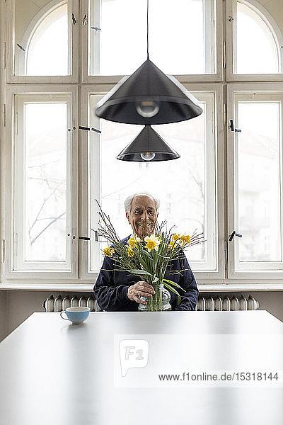 Lächelnder älterer Mann mit Blumenstrauss sitzt zu Hause am Tisch
