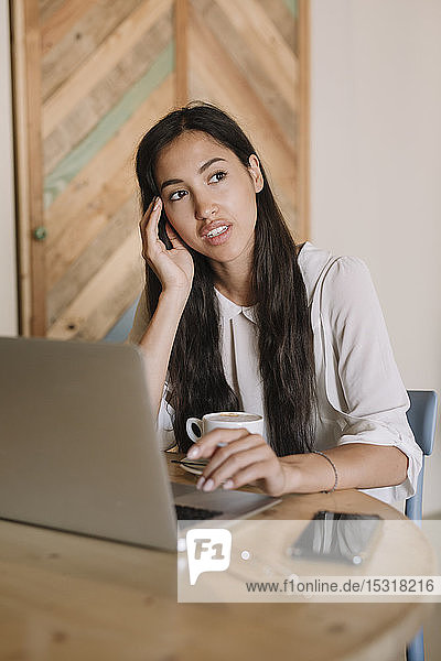 Young businesswoman with laptop at table in a cafe having a break