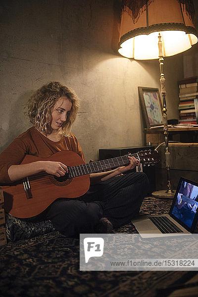 Junge Frau sitzt mit Gitarre auf dem Boden und schaut auf den Laptop