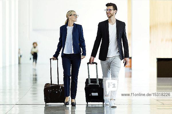 Zwei lächelnde junge Geschäftspartner beim Spaziergang am Flughafen