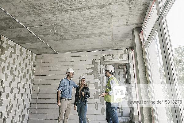 Architekt im Gespräch mit künftigen Eigentümern auf der Baustelle