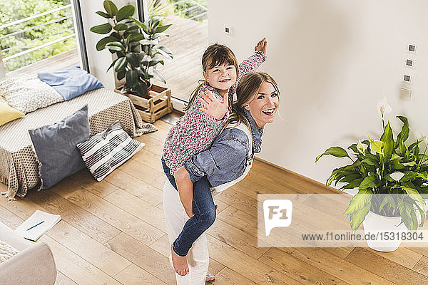 Happy mother carrying daughter piggyback at home