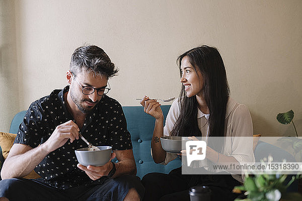Young couple siiting on a couch in a cafe having breakfast