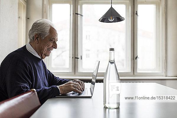 Lächelnder älterer Mann mit Laptop auf dem Tisch zu Hause