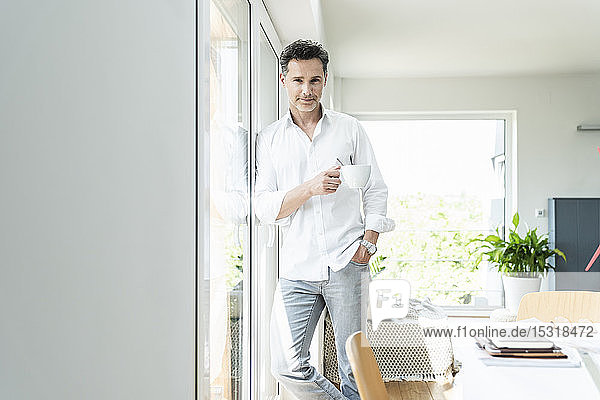 Mature man leaning on window  drinking coffee at home