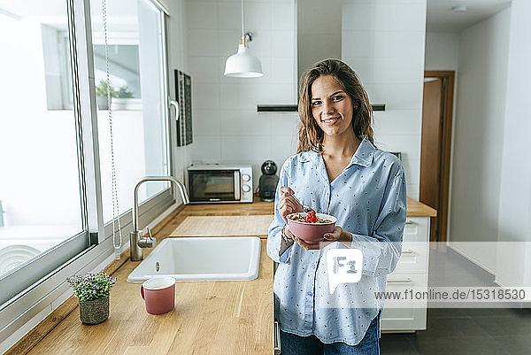 Porträt einer jungen Frau,  die einen Pyjama trägt und zu Hause in der Küche Müsli isst