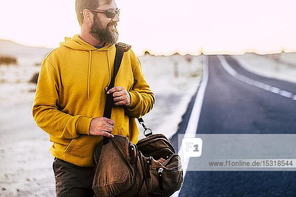 Mann mit gelbem Kapuzenpullover und braunem Korb auf einer Straße