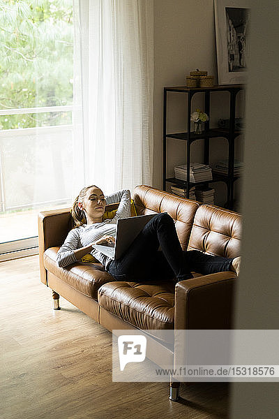 Junge Frau liegt zu Hause mit Laptop auf der Couch