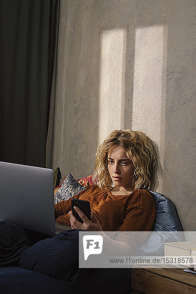 Portrait of blond young woman lying on bed using cell phone and laptop
