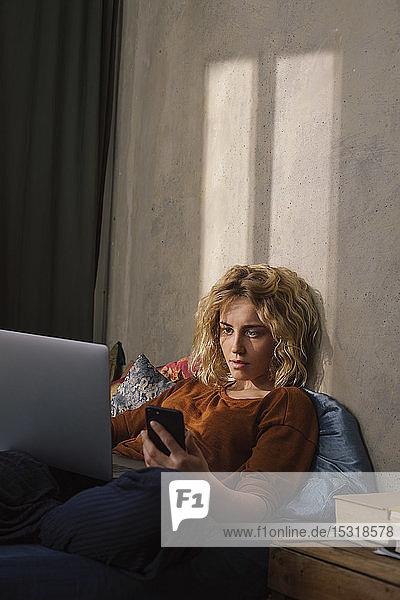 Porträt einer blonden jungen Frau  die mit Handy und Laptop auf dem Bett liegt