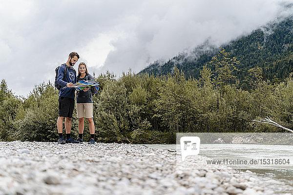 Junges Paar auf einer Wanderung am Flussufer beim Kartenlesen  Vorderriss  Bayern  Deutschland