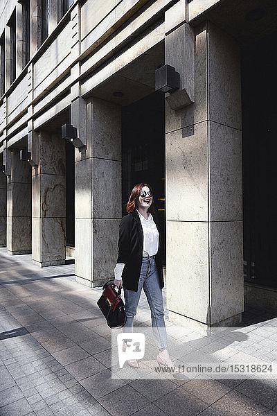 Geschäftsfrau  die auf der Straße geht  Tragetasche