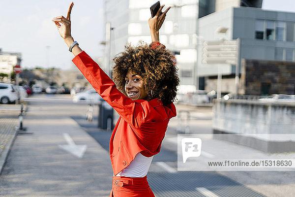 Porträt einer glücklichen jungen Frau im modischen roten Hosenanzug mit Siegeszeichen
